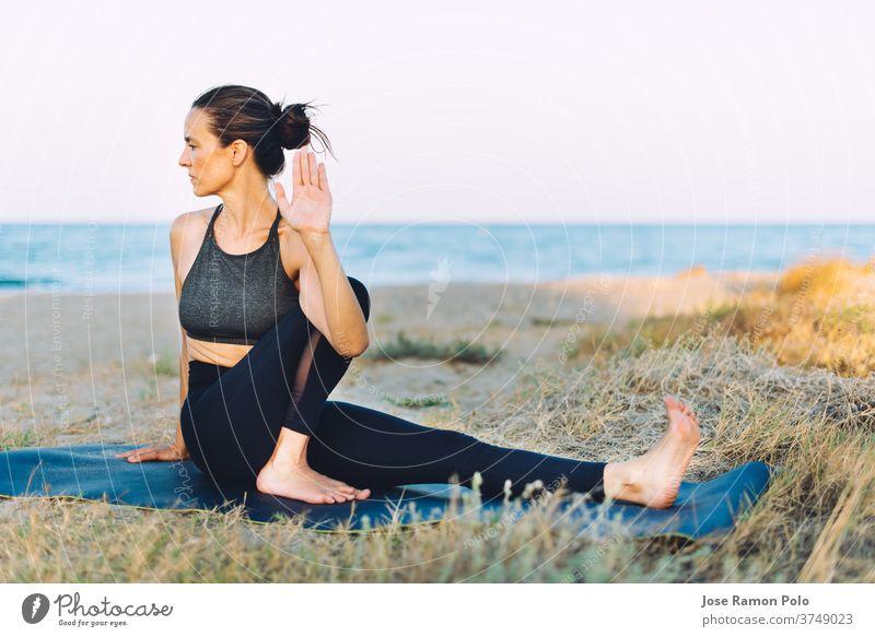 junge Frau, die Yoga-Übungen auf dem Boden im Freien am Meer macht Menschen Gesunder Lebensstil Gleichgewicht trainiert. Lebensstile eine Person Sonnenlicht