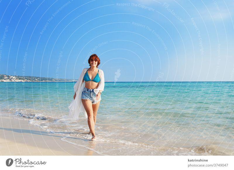 Junge Frau in Bedeckung und Jeans-Shorts am Strand spazieren jung zudecken Kimono weiß blau türkis Jeanshose laufen hohe Taille reisen Ferien Konzept