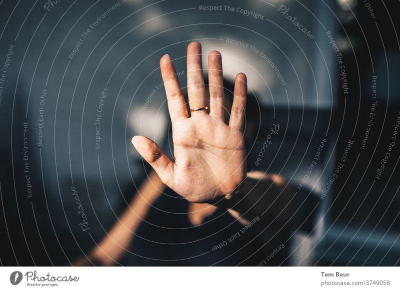 Stop! Frau hält ihre Hand, mit der Handfläche nach aussen, mit einer  Stop Geste nach oben, am Mittelfinger ein goldener Ring geste Gesten Farbfoto
