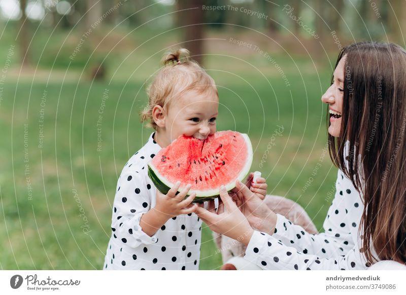 glückliche Mutter und Tochter essen Wassermelone im Sommerpark. Glücklich lächelnde Familie isst Wassermelone im Park. Mutter und Tochter verbringen Zeit miteinander. Diät, Vitamine, Konzept für gesunde Ernährung. selektiver Fokus