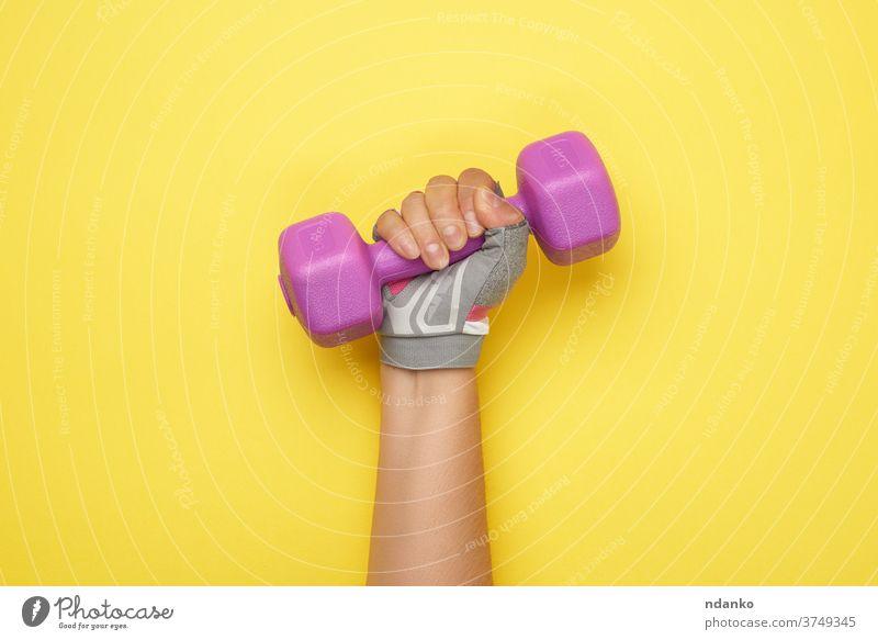 weibliche Hand in einem rosa Sporthandschuh hält eine violette, ein Kilogramm schwere Hantel Handschuh Kurzhantel Gerät Übung passen Fitness Ausrüstung