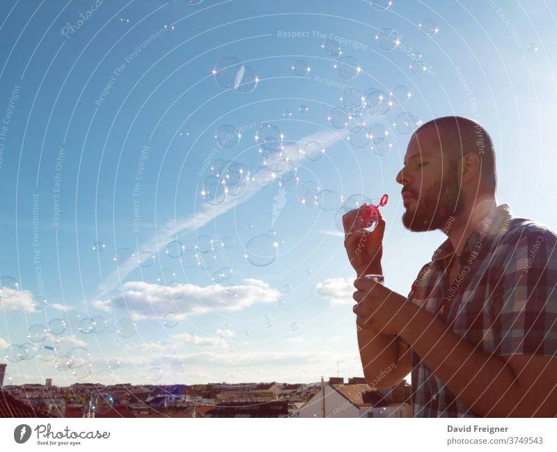 Mann bläst Seifenblasen von seinem Balkon. Ausgangsbeschränkung Quarantäne wegen Coronavirus, Home-Office und Social-Media-Konzept Blasen Terrasse Schlag