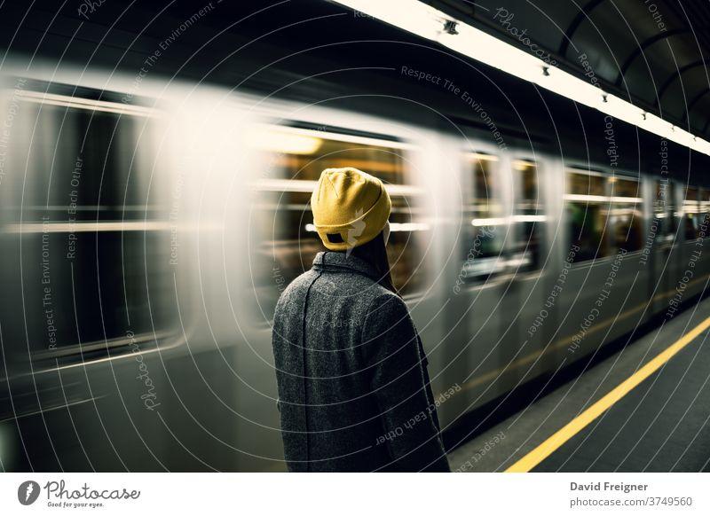 Junge Frau wartet an der U-Bahn-Station, während der Zug eintrifft. Ankunft Großstadt Abheben Eisenbahn Pendler Wagen schnell Licht Ausflug warten Nachlauf