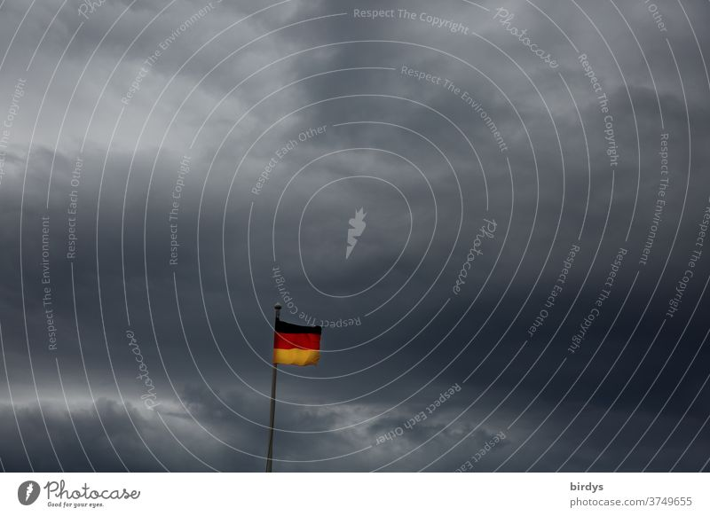 kleine Deutschlandfahne vor Gewitterwolken, düsteres Szenario, Deutschlandflagge Deutsche Flagge Nationalflagge Politik & Staat Wind wehen dunkle Wolken