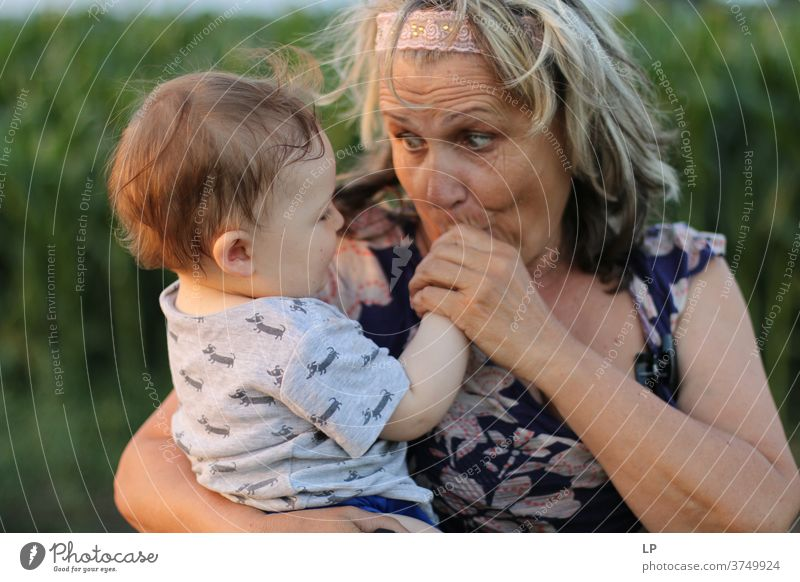 Oma hält kleines Kind und küsst seine Hände Porträt Liebe Liebkosen Wahrheit Vertrauen Lebensfreude Fröhlichkeit Gefühle Kindheit Paar Familie & Verwandtschaft