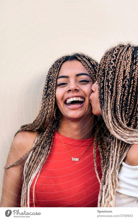 Liebe afroamerikanische Schwestern Kuss einen Kuss geben afrikanische Mädchen Vorderansicht in die Kamera schauen Geschwister Zopf Afroamerikaner Straße