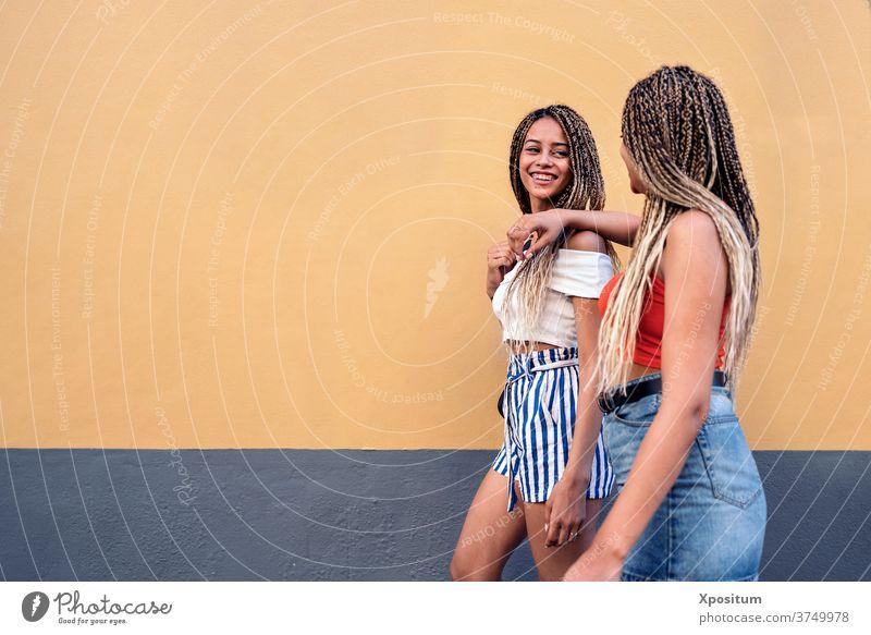 Coole Schwestern haben Spaß Seitenansicht laufen Straße Zopf ethnisch rassisch die sich gegenseitig ansehen Lächeln urban Frauen Porträt zwei Frauen Hintergrund