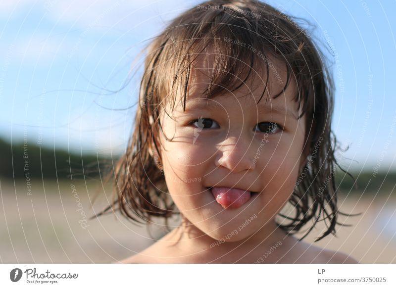 kleines Mädchen, das seine Zunge herausstreckt Blick in die Kamera Oberkörper Porträt Sonnenuntergang Sonnenaufgang Sonnenstrahlen Sonnenlicht Licht