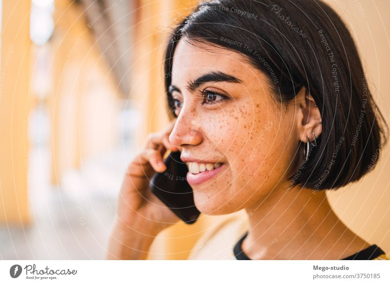 Junge Lateinamerikanerin am Telefon. sprechend Mobile Frau Mädchen im Freien Person Anruf klug Zelle jung brünett Großstadt Smartphone Funktelefon Gespräch