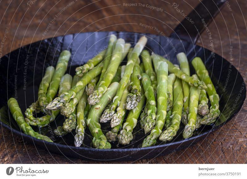 frischer grüner Spargel in einer Pfanne auf dunklem Holz Eisenpfanne Planke Saison saisonal Gourmet String Küche Zutaten Antioxidans gesund Essen Sprossen