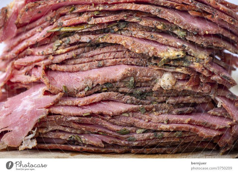 Stapel von in Scheiben geschnittenem Pastrami-Fleisch Rindfleisch brisket rustikal geStapelt Nahaufnahme rot Deli schneiden kalt gefaltet dünn geröstet Essen