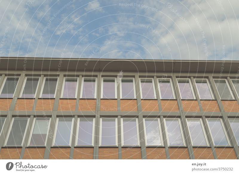 Fassade eines Hauses mit vielen Fenstern aus der Froschperspektive mit einem Stück Himmel Hausfassade hoch Gebäude Architektur Flachdach Wolken Bauwerk Wand