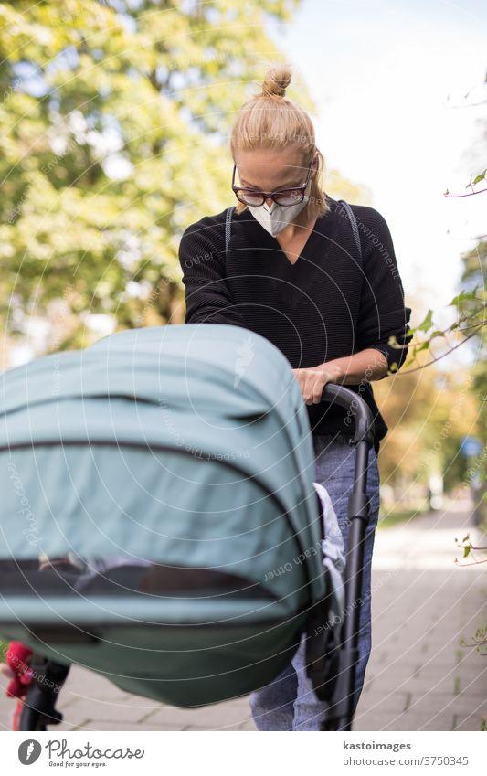 Besorgte junge Mutter, die auf einer leeren Straße mit einem Kinderwagen unterwegs ist und medizinische Masken trägt, die sie vor dem Coronavirus schützen sollen. Sozial distanziertes Leben während einer Coronavirus-Pandemie