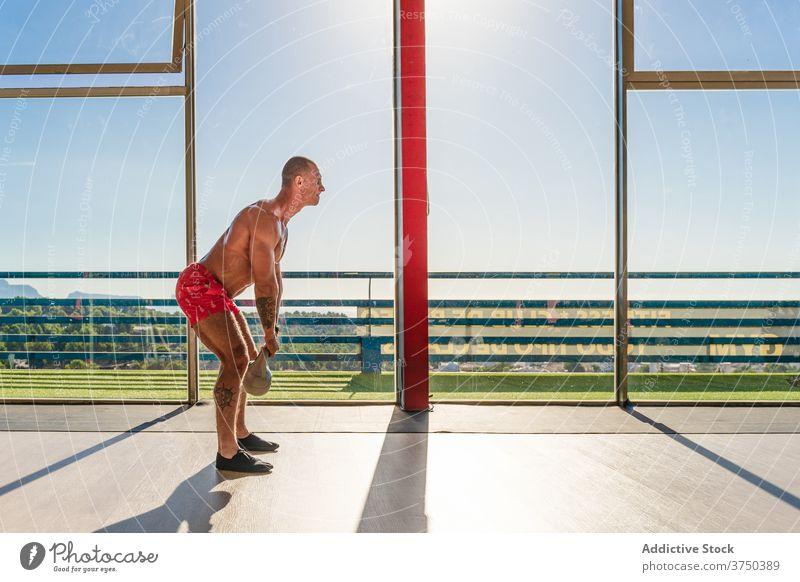 Athletischer Mann Training mit Kettlebell im Fitnessstudio Übung schwer Ausdauer stark Sportler muskulös männlich geräumig intensiv Körper passen Bestimmen Sie