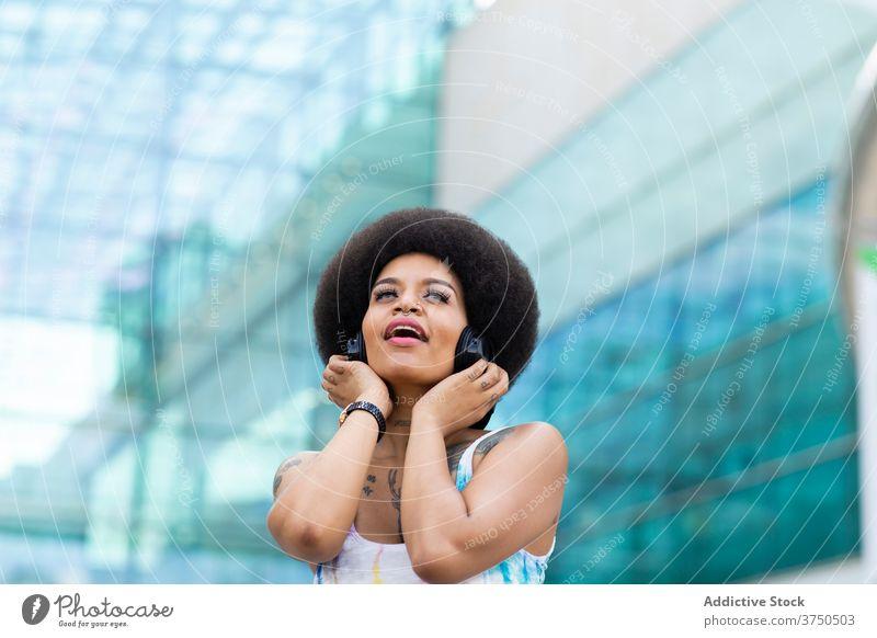 Verträumte schwarze Frau, die mit Kopfhörern Musik hört zuhören verträumt sorgenfrei genießen Gesang Großstadt urban ethnisch Afroamerikaner Afro-Look Frisur