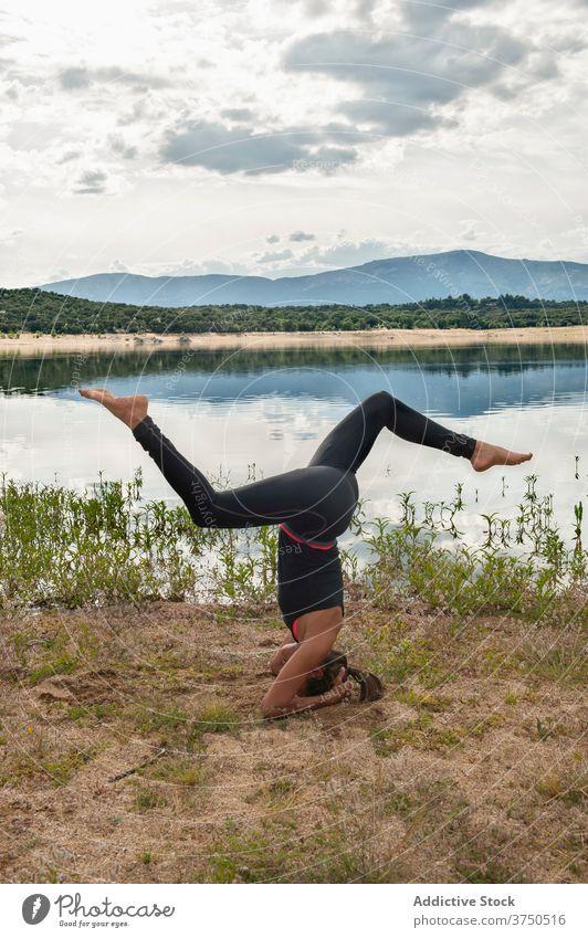 Frau übt Kopfstand Yoga-Pose in der Nähe von See üben sirsasana Asana Gleichgewicht Umkehrung Variation fortgeschritten Harmonie Wellness Lifestyle beweglich