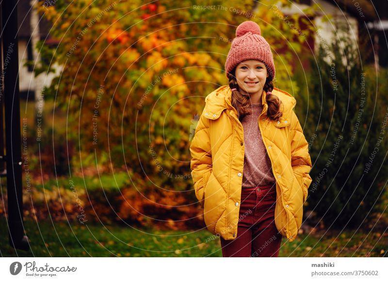 niedliches Mädchen, das im Herbst im Garten oder Park spazieren geht und warme, stilvolle Kleidung trägt Kind Saison Spaß Natur im Freien Freude Glück Kindheit