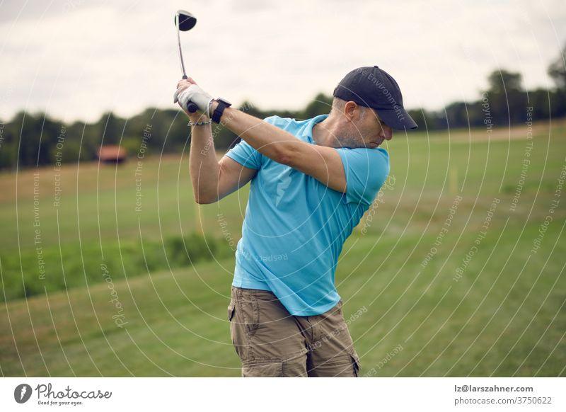 Mann, der Golf spielt und den Ball schwingt, während er seinen Schlag mit einem von hinten gesehenen Driver ausführt, der in einem gesunden, aktiven Lebensstilkonzept das Fairway hinunterblickt