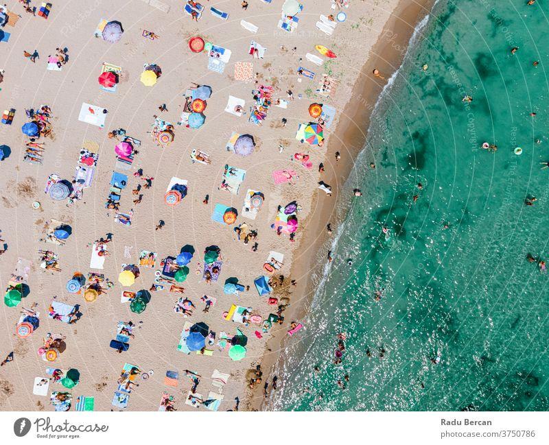Strandfotografie aus der Luft, Menschen und farbenfrohe Regenschirme am Meeresstrand Antenne Ansicht Sand Hintergrund Wasser MEER Urlaub blau reisen mediterran