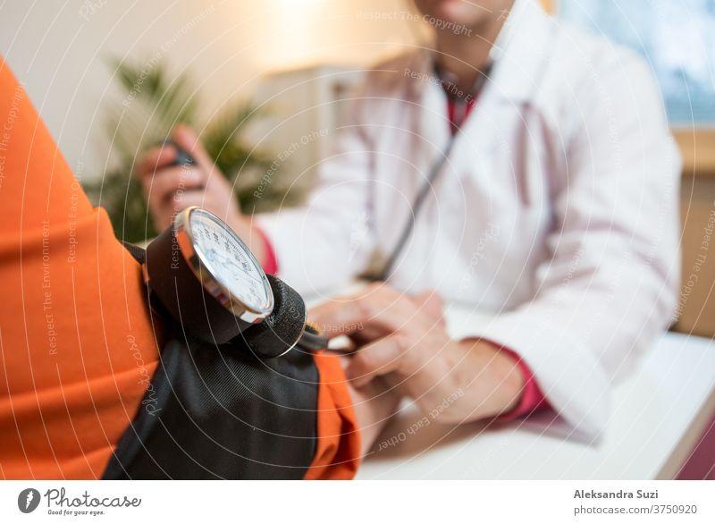 Arzt misst den Blutdruck einer Patientin im Krankenhausbüro. Kranke ältere Frau, die einen Arzttermin hat. Nahaufnahme Pflege geduldig abstützen alt Senior