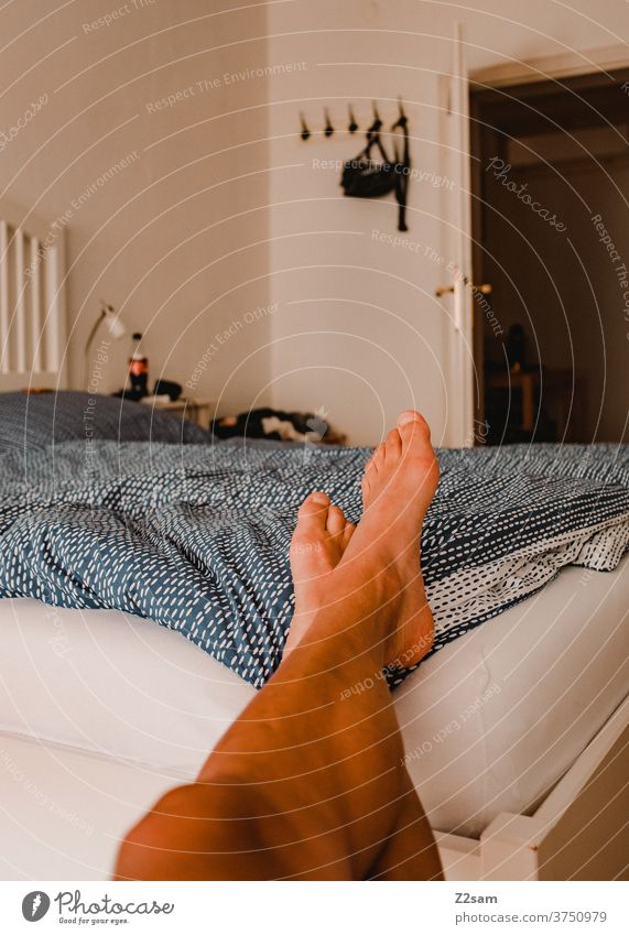 Junger Mann entspannt im Schlafzimmer Bett zuhause erholung entspannung wohnen gemütlich altbau liegen ausruhen schreiben entspannen wochenende freizeit Morgen