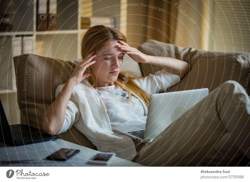 Attraktive Geschäftsfrau auf einer Couch mit zwei Mobiltelefonen und Laptops. Erschöpfte Frau im Büro spät in der Nacht. Verantwortliche Führungskraft bei der Arbeit, Kopfschmerzen, Hände an den Schläfen