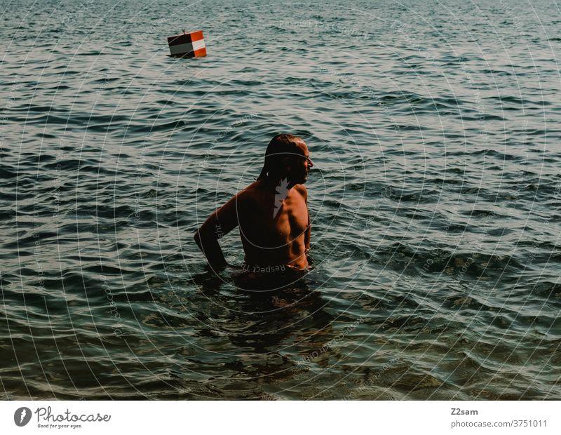 Junger Mann badet im See baden mann sommer sonne schatten licht wasser see gewässer türkis boje Schwimmen & Baden Reflexion & Spiegelung