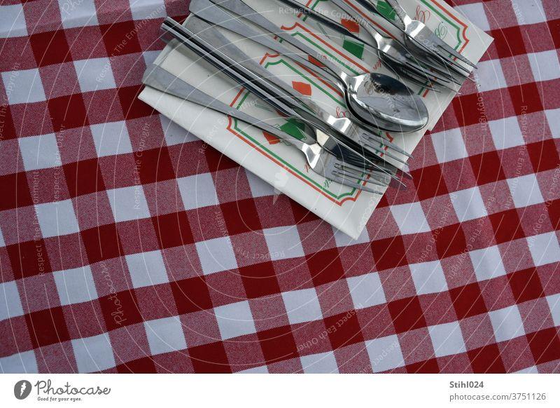 Besteck liegt auf Serviette auf rot-weiß karierter Tischdecke Restaurant coperto Gedeck Draufsicht italienisch Pizzeria Messer GAbel Löffel Set Essen Mahlzeit