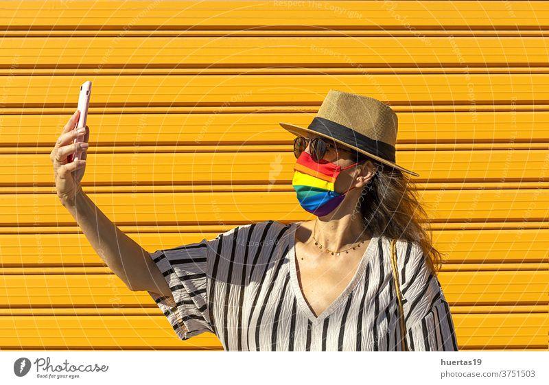 Frau mittleren Alters, die eine regenbogenfarbene Schutzmaske trägt. LGTB.Covid-19-Konzept Regenbogen lgbt Fahne Coronavirus Menschen Lifestyle Transgender