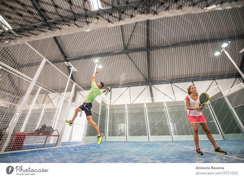 Paddle-Tennis-Training in der Halle. Weitwinkelansicht unter dem Netz Paddeltennis Padel Sport Erholung Klasse Gericht Mann Frau Frauen Männer blau Lebensstile