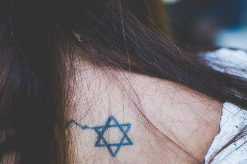 Der Davidstern, Symbol des Judentums, als Tattoo auf dem Rücken einer Frau mit langen braunen Haaren Religion religiös Glaube gläubig Jugenich Junge Frau