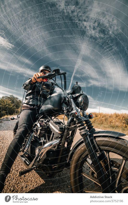 Brutal Biker sitzt auf Motorrad in der Landschaft Mitfahrgelegenheit Laufwerk Mann Straße Kraft Reiter brutal Geschwindigkeit schnell reisen Freiheit Verkehr