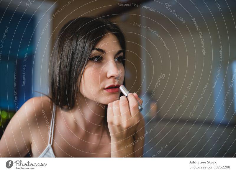 Konzentrierte Frau beim Schminken zu Hause bewerben Lippenstift Make-up heimwärts vorbereiten Party Veranstaltung Fokus Gesicht Kosmetik sanft charmant