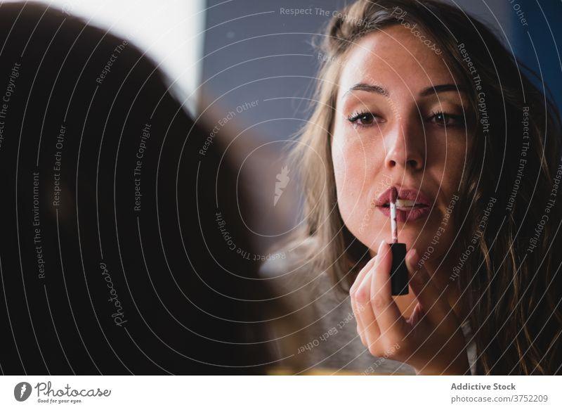 Konzentrierte Frau beim Schminken zu Hause bewerben Lippenstift Make-up heimwärts vorbereiten Party Veranstaltung Fokus Gesicht Kosmetik sanft charmant frisch