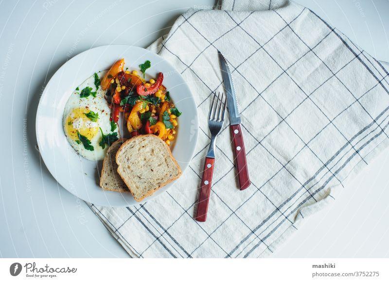 schmackhaftes vegetarisches Frühstück nach Bauernart - Spiegelei mit gebackenem Paprika und Mais mit Petersilie und Vollkornbrot auf weißem Teller serviert Ei