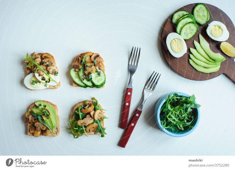 verschiedene vegetarische Toasts am Morgen, die mit Pilzen, Avocado, Rucola, Gurke und Eiern serviert werden. Gesundes Essen auf weißem Hintergrund Zuprosten