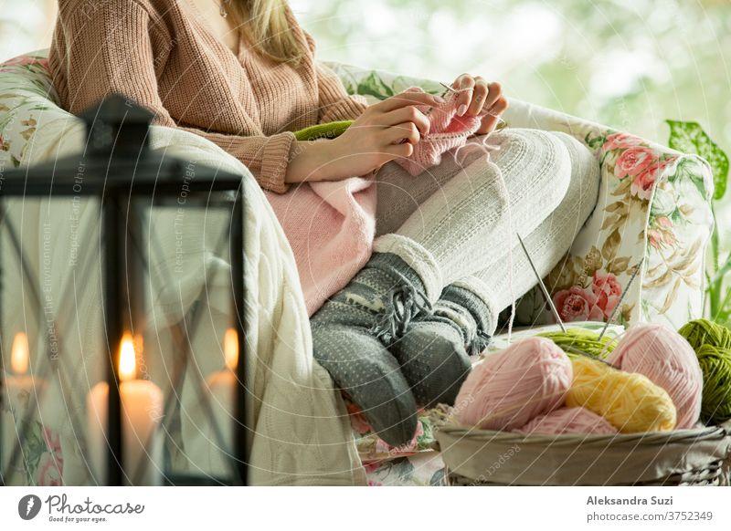 Junge Frau sitzt zu Hause auf einem Stuhl am Fenster, trägt einen gestrickten warmen Pullover und strickt mit Nadeln. Gemütliches, mit Laternen und Kerzen dekoriertes Zimmer. Szenische Winteransicht von Kiefern im Schnee im Fenster