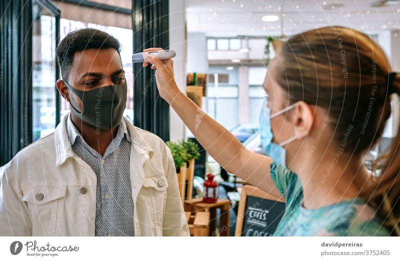 Geschäftsinhaber überprüft Kunden auf Fieber Frau Überprüfung Temperatur Mann Infrarot-Thermometer covid-19 Coronavirus Arbeitnehmer Gesichtsmaske Blick