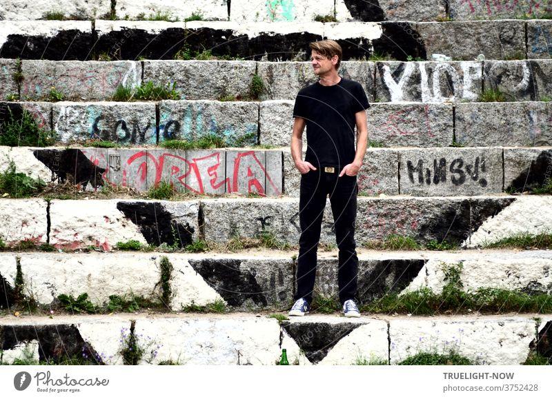 Tim Trzoska, Berlin Fotograf,  Berlin Kenner von Geburt, steht in schwarzen Jeans, schwarzem T-Shirt und leichten Sneakers auf mit Graffiti bemalten Stein-Stufen am Mauerpark in Berlin Prenzlauer Berg