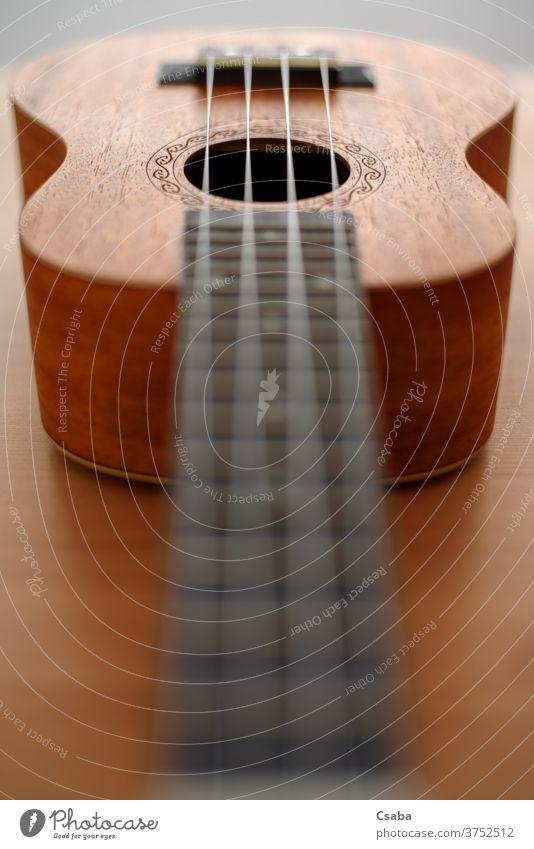 Braune Ukulele mit geringer Schärfentiefe Instrument akustisch hölzern Musical Schnur braun Holz Gitarre Musik Hintergrund Rosette hawaiianisch Objekt Kunst