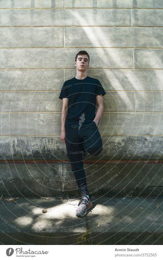 Porträt eines kühlen, stehenden jungen Mannes, der an eine Wand gelehnt ist Stehen Lehnen Grunge selbstbewusst ernst Sportbekleidung Schmutz im Freien Teenager