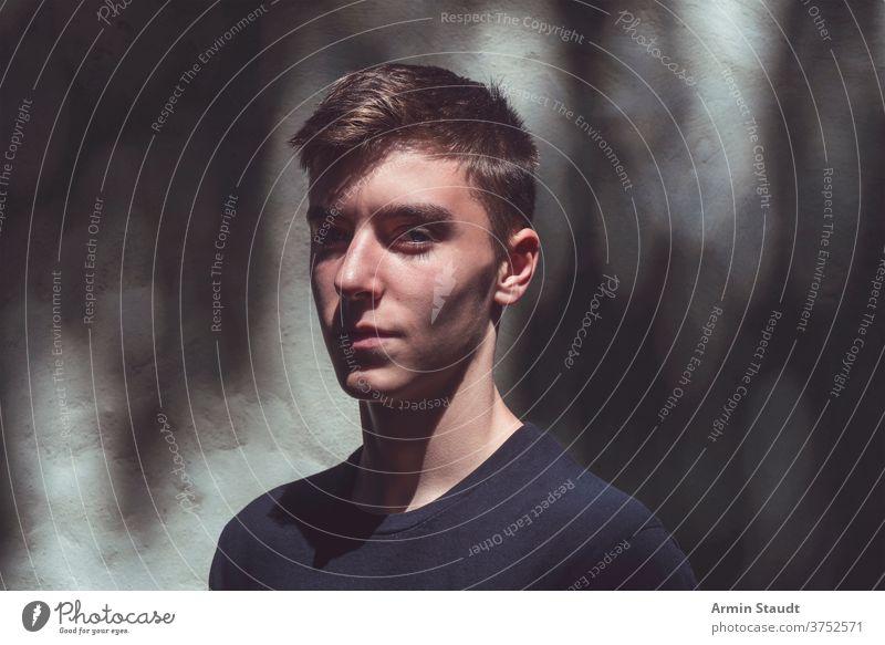 Porträt eines selbstbewussten jungen Mannes, der im Schatten steht Lächeln geheimnisvoll dunkel Sonnenlicht stolz Nahaufnahme Wand cool Stehen Grunge Schmutz