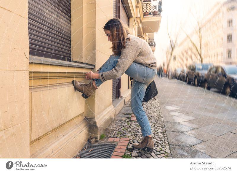 junge Frau bindet ihren Schuh auf der Straße Porträt im Freien Straßenbelag Autos Großstadt Stadt urban hockend Schuhe Sommer schön konzentriert Tasche Wand