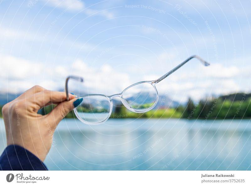 Brille vor schöner Natur kurzsichtig Blick Auge Sehvermögen Brillenträger Optiker Augenheilkunde Gesundheit Farbfoto Glas See Panorama (Aussicht) halten Hand