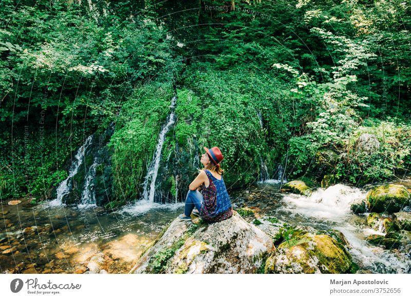 Junge weibliche Naturforscherin geniesst an den Wasserfällen Abenteuer schön Kaskade lässig Kaukasier entdecken Fundstück genießen erkunden Frau fließen