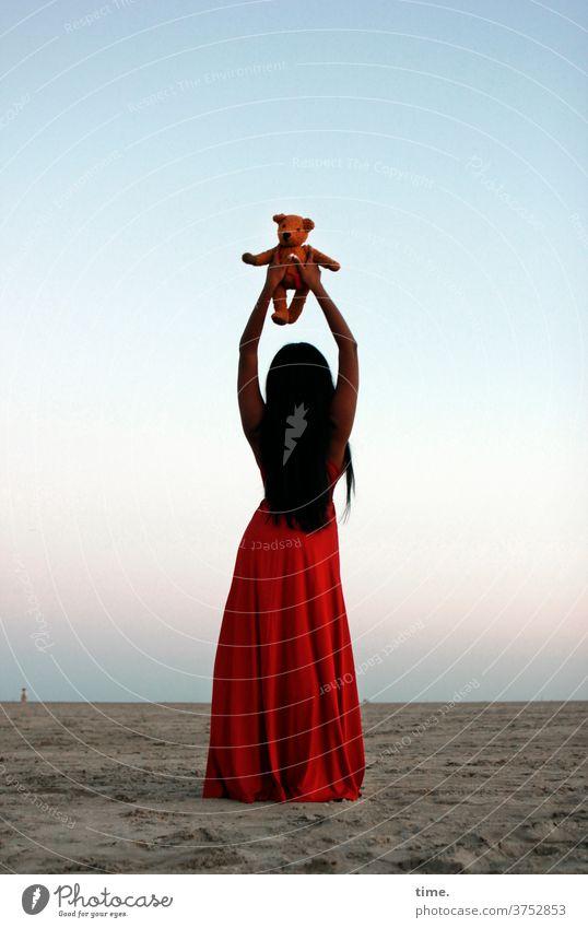 spirit in a material world abend stimmung dunkelhaarig langhaarig kleid strand himmel nordsee rot elegant weiblich halten frau teddy kinderspielzeug stofftier