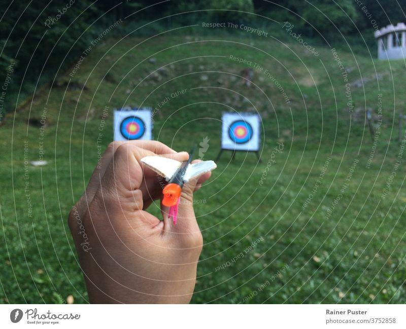 Hand hält einen Pfeil mit zwei Zielen im Hintergrund Alternativen Bogenschütze Schleife Geschäftsstrategie Beschluss u. Urteil Finger Fokus Spaß Apparatur Spiel