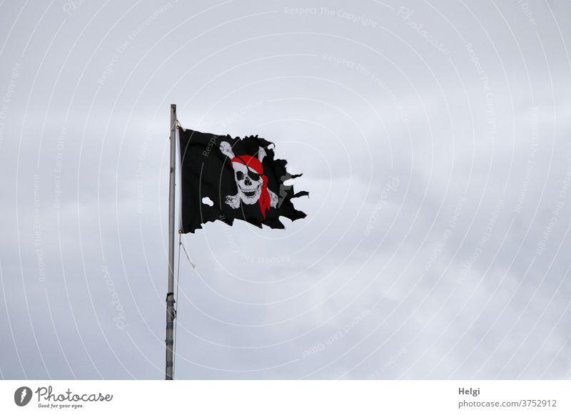 dynamisch | ausgefranste Piratenflagge flattert an einer Fahnenstange im stürmischen Wind vor dicken grauen Wolken Flagge Fahnenmast windig Himmel Regenwolken