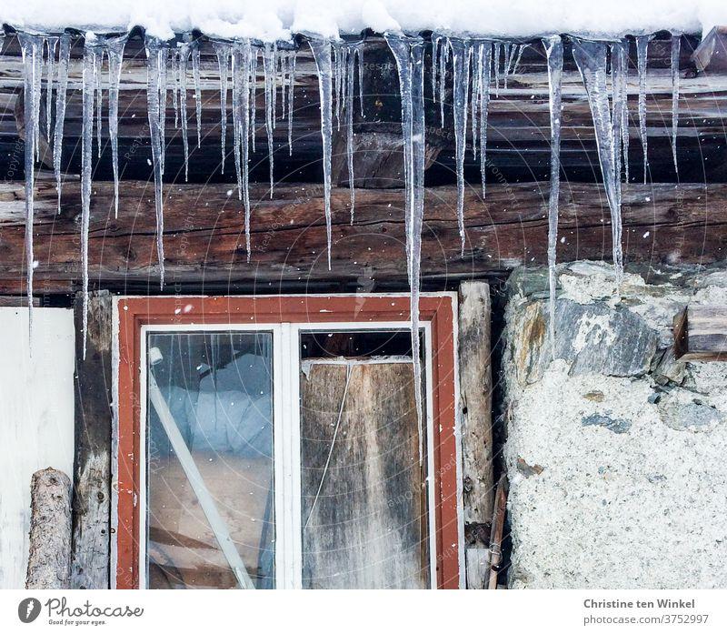 Lange Eiszapfen hängen vom Dach einer alten Hütte. Detailansicht mit rotem Fensterrahmen, Steinen und Holzbalken Frost Winter Winterstimmung Steinwand Eiszeit