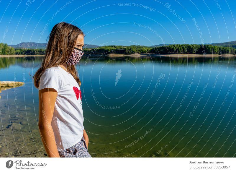 Mädchen mit weissem T-Shirt und einer Maske zum Schutz vor dem Coronavirus, das in einem See posiert, in dem sich der Wald im Wasser spiegelt niedlich jung